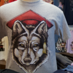 Branded merchandise for sale, including a t-shirt with a wolf wearing a mortarboard.