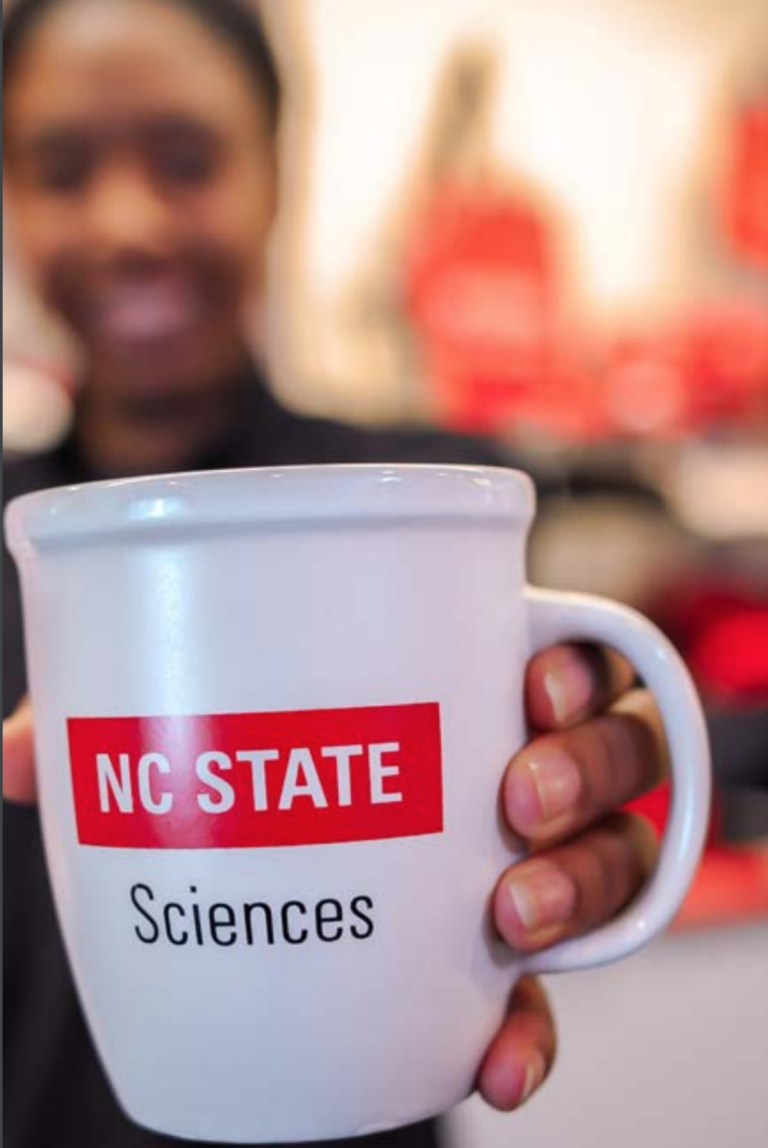 An NC State Sciences-branded coffee mug.