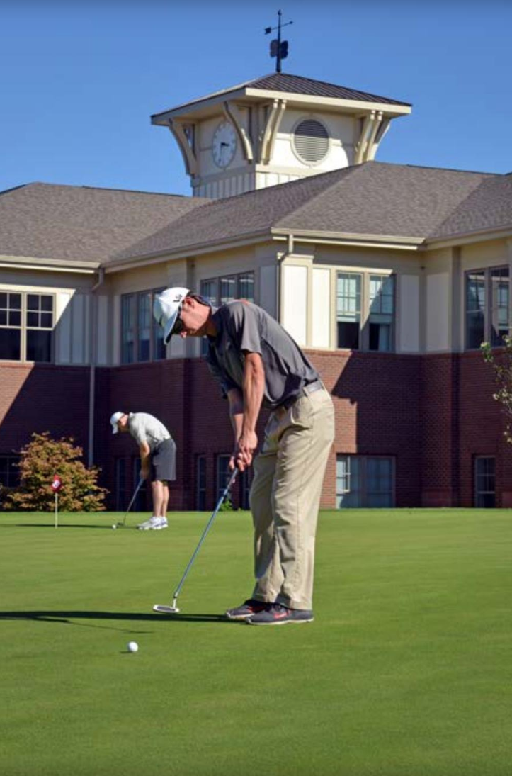 A golfer practices putting at the Lonnie Poole Golf Course.