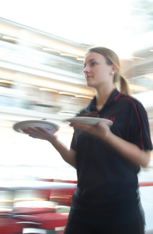 A caterer carries plates of food at a Rave-catered event.